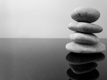 A Stack Of Zen Stones On A Black Table Against Grey Background. Concept Of Harmony, Balance And Meditation, Spa, Relax