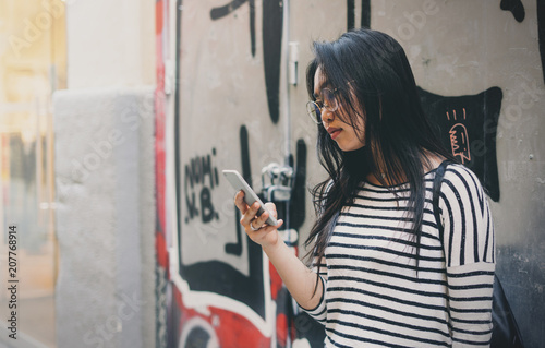 Side view of asian female in trendy eyeglasses standing on street using navigating application on a mobile phone. . Chinese woman reading messages on a smartphon while walking the city.