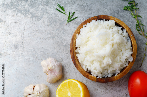 Photo  Top view image of cooked jasmin rice on metallic background with lemon, garlic a