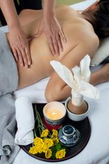 Obraz na płótnie Canvas Massage series: Therapist massaging Asian woman's back with hot wax