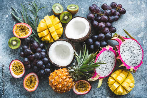 Assortment of exotic tropical fruits, top view. Passionfruit, dragonfruit, mango, pineapple, kiwi, grapes and coconut. Fresh food background. Healthy eating, vegan and summer concept