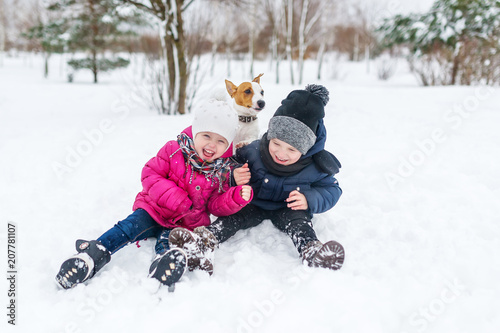 Cute children and dog playing in snow.