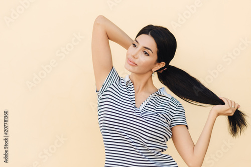 Fotografía  Pensive dark haired female makes pony tail, has full lips and pleasant appearance, wears casual outfit, stands against studio background, focused into distance