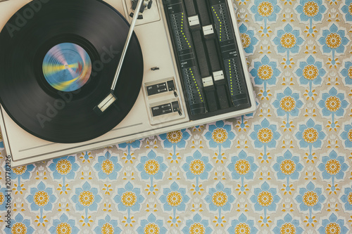 Fotografia  Record player on top of flower wallpaper