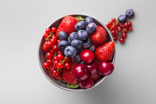 Fresh Fruit In A Metal Bowl On A Grey Background (strawberry, Blueberry, Cherry, Red Currant). Top View. Copy Space
