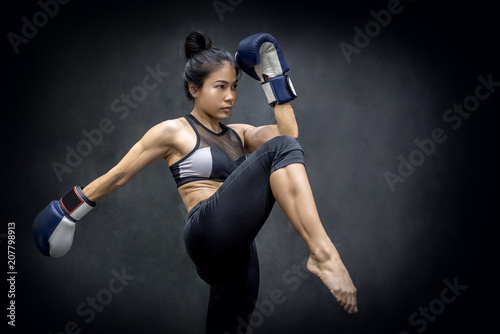 Foto op Plexiglas Vechtsport Young Asian woman boxer with blue boxing gloves kicking in the exercise gym, Martial arts on black background