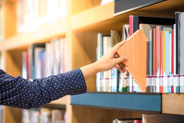 male hand choosing and picking orange book in public library, education resea...