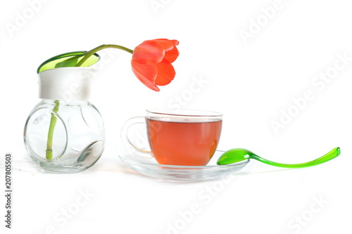 Staande foto Thee elegant curved green spoon on saucer, glass transparent cup of hot black tea and blooming red Tulip flower in sugar bowl on a white background for morning home relax