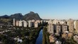 Aerial descending footage of Marapendi canal in Barra da Tijuca on a summer day, with a boat traveling along river. Tall residential skyscrapers on both sides, with Gavea Stone on the background