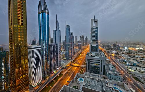 Fototapeta Dubai skyline podczas wschodu słońca z niesamowitych świateł centrum miasta i ruchu drogowego Sheikh Zayed, Zjednoczone Emiraty Arabskie.