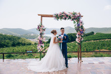 Husband And Wife Are Standing Under A Flower Arch Amid An Incredibly Beautiful Nature. The Guy Looks At His Friends And Smiles At Them, The Girl Looks At Her Husband In Love.
