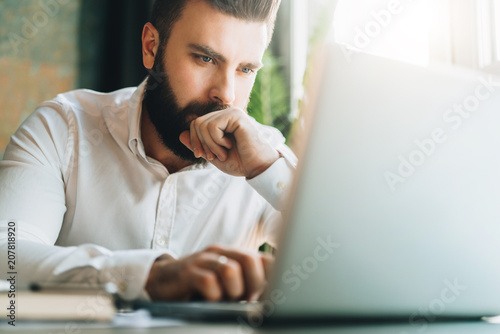 Fotomural  Young serious bearded businessman sitting in office at table and using laptop