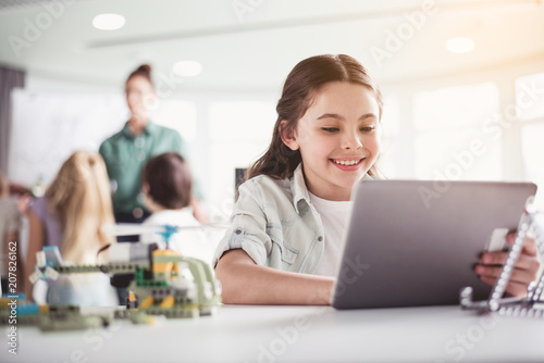 Portrait of cheerful child having fun with digital device while situating at table in classroom