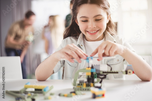 Fotografía  Portrait of satisfied little lady making helicopter from constructor while locat