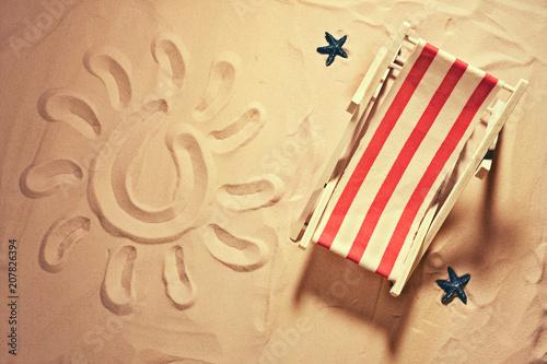 Canvas Print deckchair on a beach with a sun drawn on the sand