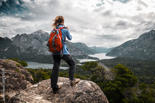 Fotografie, Obraz  Tourist hiker with red backpack takes pictures of the valley with mountains and lakes