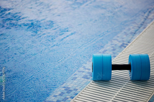 Fotografie, Obraz  The kettlebell for water aerobics lies on the edge of the pool