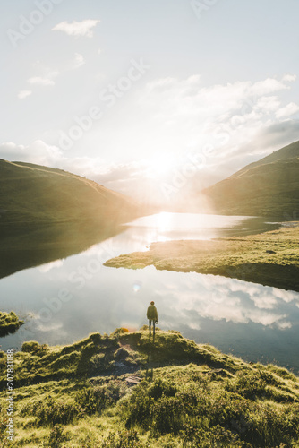 Person overlooking a sunrise over a mountain lake in Switzerland