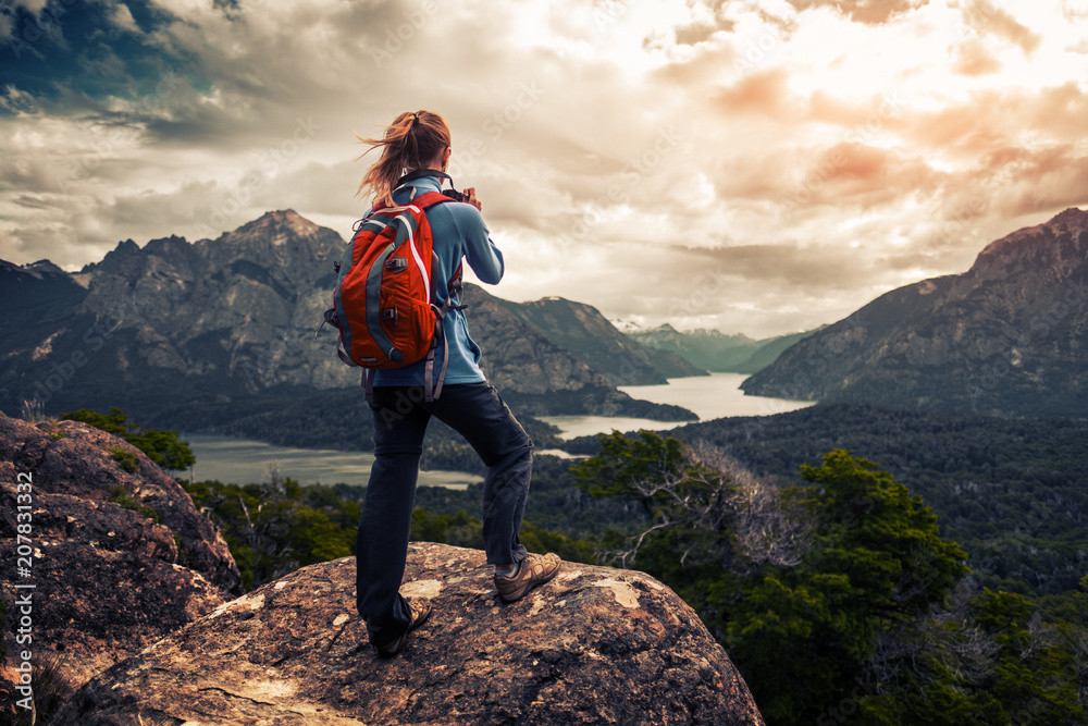 Fototapety, obrazy: Tourist hiker with red backpack takes pictures of the valley with mountains and lakes. Patagonia, Argentina