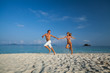 Young couple runs on the tropical beach at sunny day with sea on the background