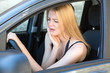blond woman having toothache while driving car