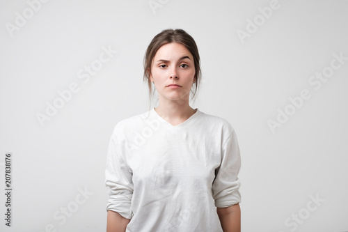 Portrait of caucasian woman with serious facial emotion like she is asking what Wallpaper Mural