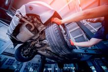Car Mechanic Inspecting Wheel ...