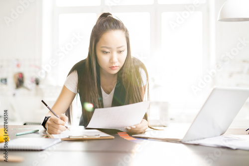 Fotografía  Portrait of focused creative Asian woman drawing sketches for while standing at