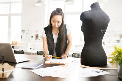 Fotografía  Waist up portrait of focused Asian woman working in fashion design and drawing s