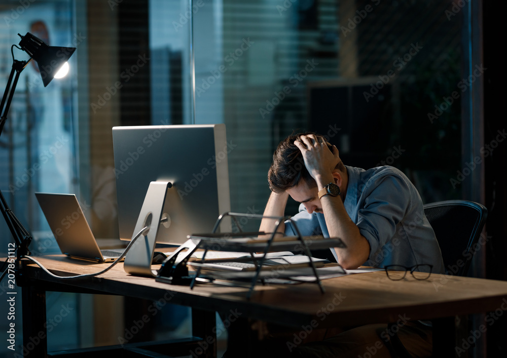 Fototapeta Young man in shirt working alone in office late sitting in lamplight at table and looking sleepy.