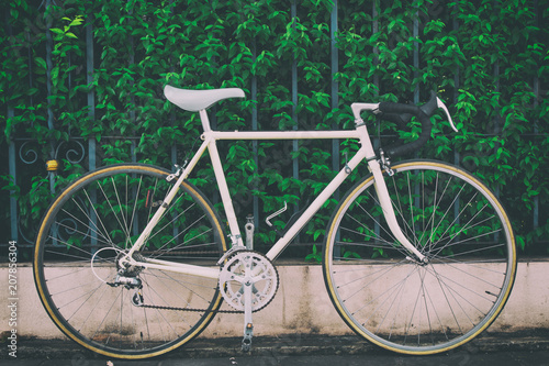 Deurstickers Fiets Vintage road bike on bush background, picture in vintage tone