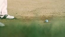 Shot Of A Man Golfer On A Sand Golf Course Preparing For Hits With Green Grass