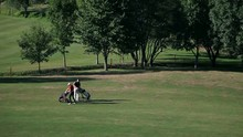 Slide Shot Of A Couple That Come On The Golf Course And Starts Preparing For