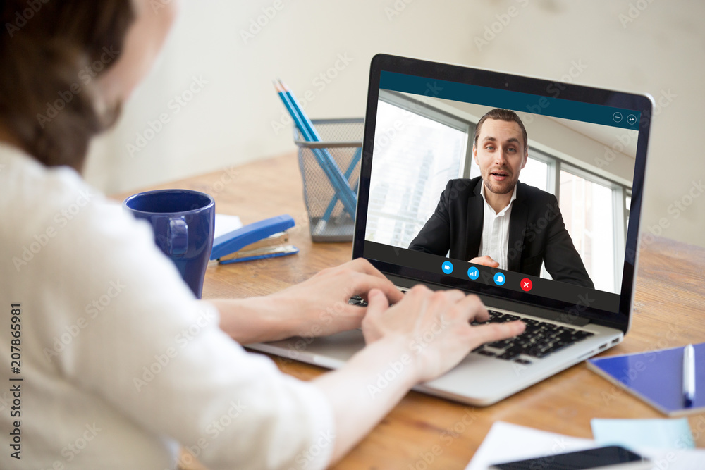 Fototapeta Businesswoman making video call to business partner using laptop. Close-up rear view of young woman having discussion with corporate client. Remote job interview, consultation, online meeting concept.