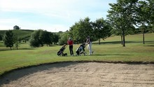 Shot Of A Couple On A Sand Golf Course Carring All The Golf Equipment And