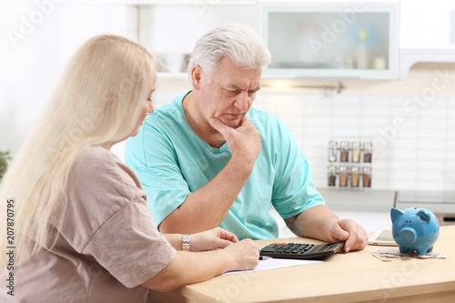 Fotografía  Mature couple thinking over pension payment at home