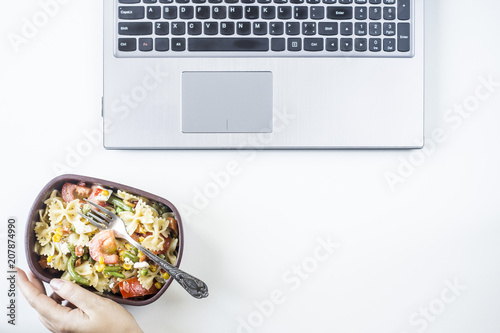 Foto op Aluminium Assortiment Container with salad with pasta in the workplace near the computer. Lunch in the office during a break between work. Woman take a food. Top view, flat lay