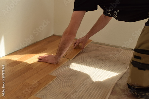 Obraz close up of worker installing wood parquet - fototapety do salonu
