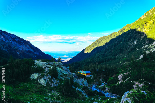 Beautiful alpine high mountains peak, blue sky background. Amazing Mountain hiking paradise landscape, summertime.