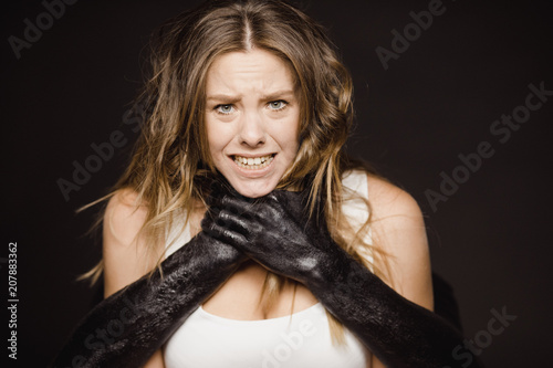 Valokuva  Concept photo of young frightened girl being chocked by terrifying black hands f