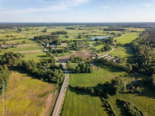 Tuinposter Honing drone image. asphalt road surrounded by pine forest and fields from above