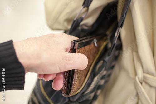 Fotografía  Pickpocket thief is stealing purse from handbag. selective focus