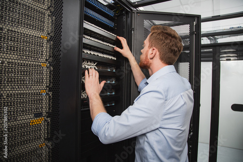 Confident IT Technician Examining Server Closet While Standing