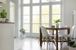 canvas print picture - White chairs at wooden table with plant in bright dining room interior with window. Real photo
