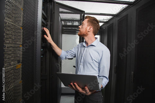 Computer programming. Confident IT technician examining server closet while carrying laptop