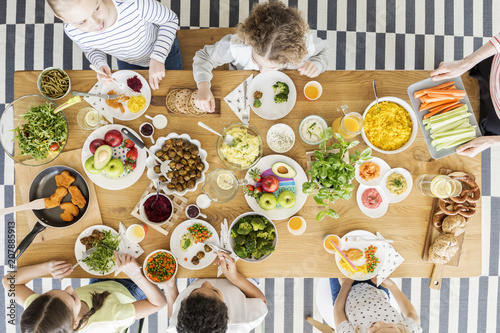 Top view on children eating healthy food during friend's birthday party