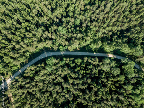 Foto op Plexiglas Groene drone image. gravel road surrounded by pine forest from above
