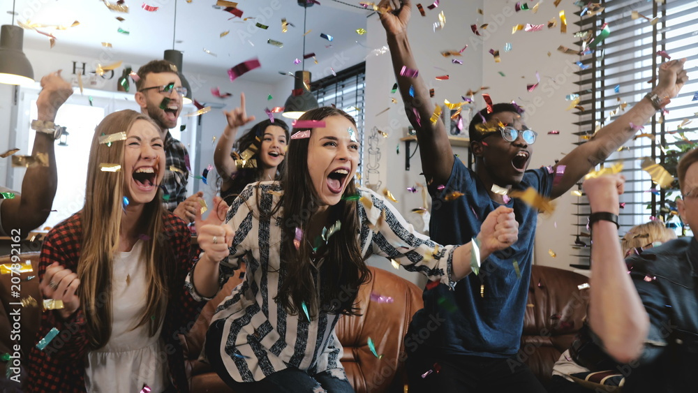Fototapeta Emotion. Multi-ethnic fans celebrate winning. Confetti 4K slow motion. Passionate supporters shout watching game on TV.