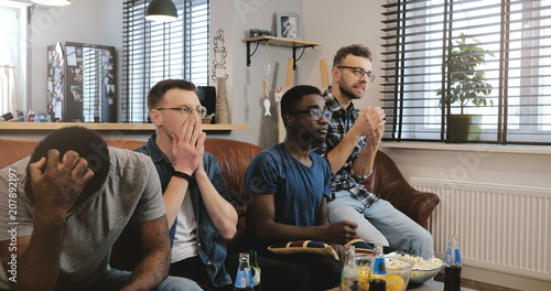 Fotografie, Tablou Multi ethnic men disappointed watching sports game