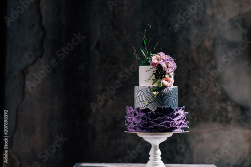 Closeup of white wedding cake with flowers on top Fotobehang